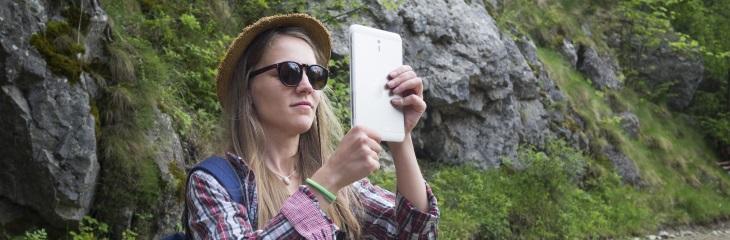 Toerist maakt foto met tablet in bergen